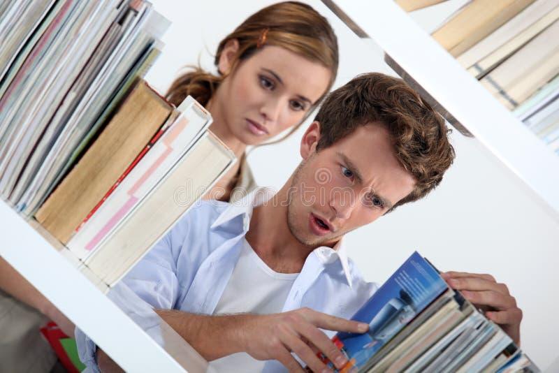 Homem que olha livros imagem de stock