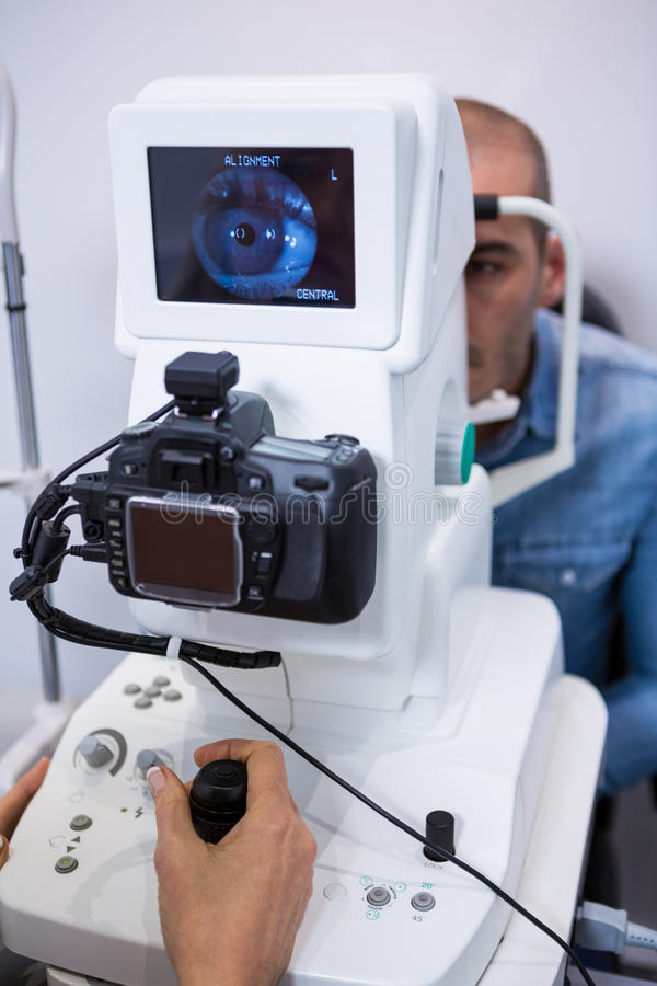Homem que olha a máquina do teste do olho imagem de stock
