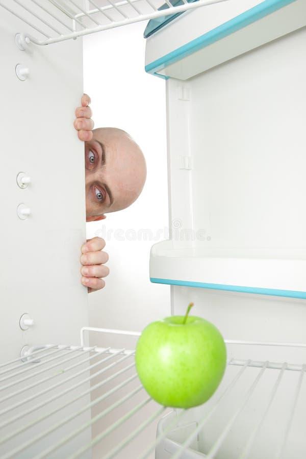 Homem que olha a maçã no refrigerador imagem de stock royalty free