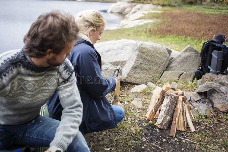 Homem que olha a mulher que desbasta a madeira no acampamento foto de stock