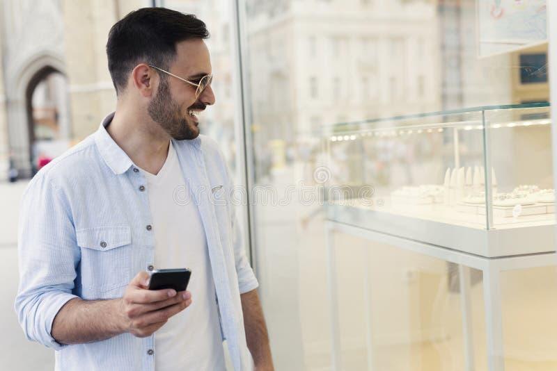 Homem que olha na janela de loja imagem de stock