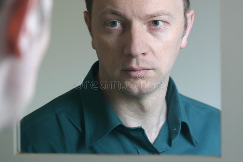 Homem que olha no espelho imagens de stock