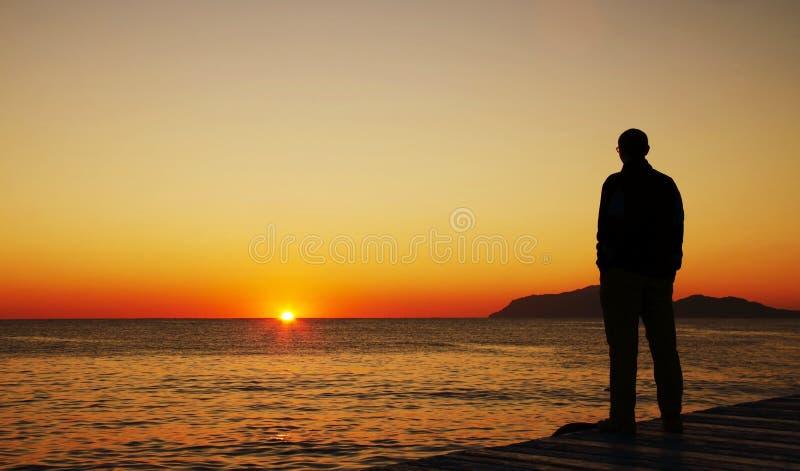 Homem que olha no por do sol imagens de stock