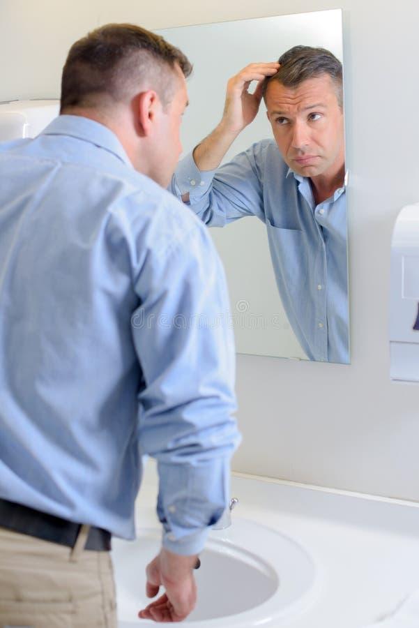 Homem que olha o cabelo no espelho imagens de stock royalty free