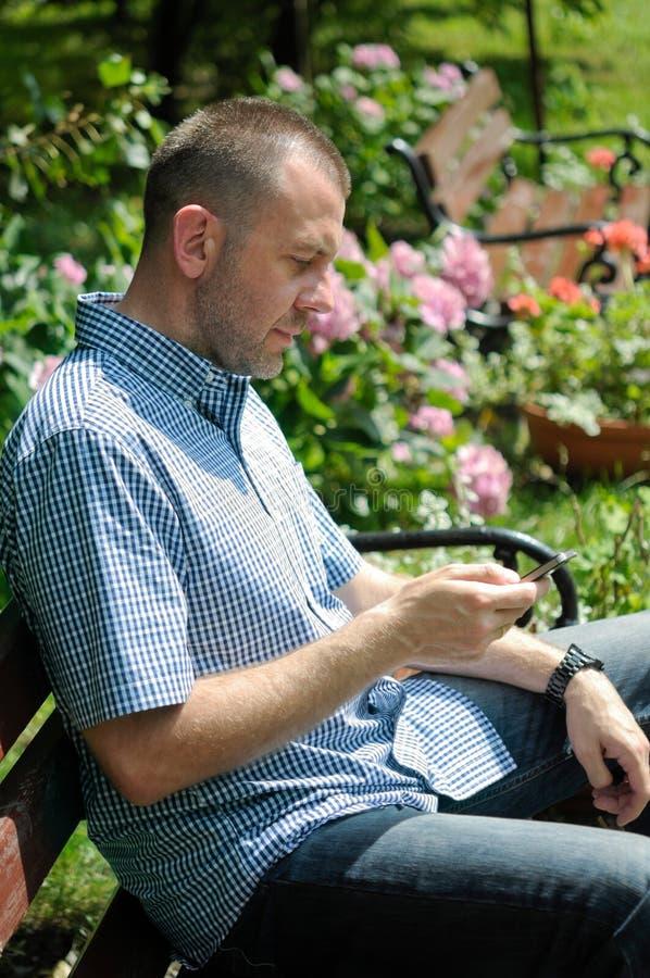 Homem que olha o smartphone imagem de stock royalty free