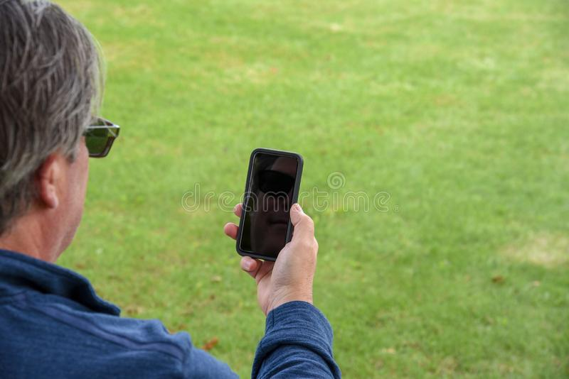 Homem que olha o telefone, vista traseira fotos de stock royalty free
