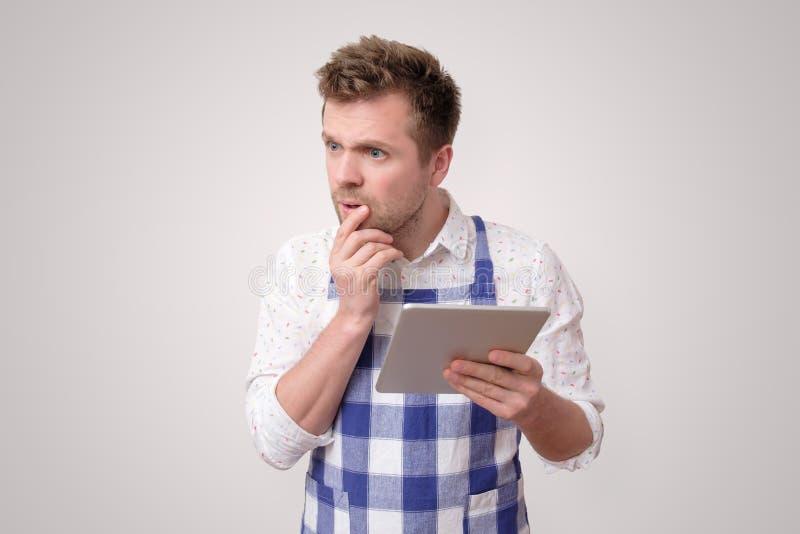 Homem que olha a receita na tabuleta digital para preparar o bolo imagens de stock royalty free