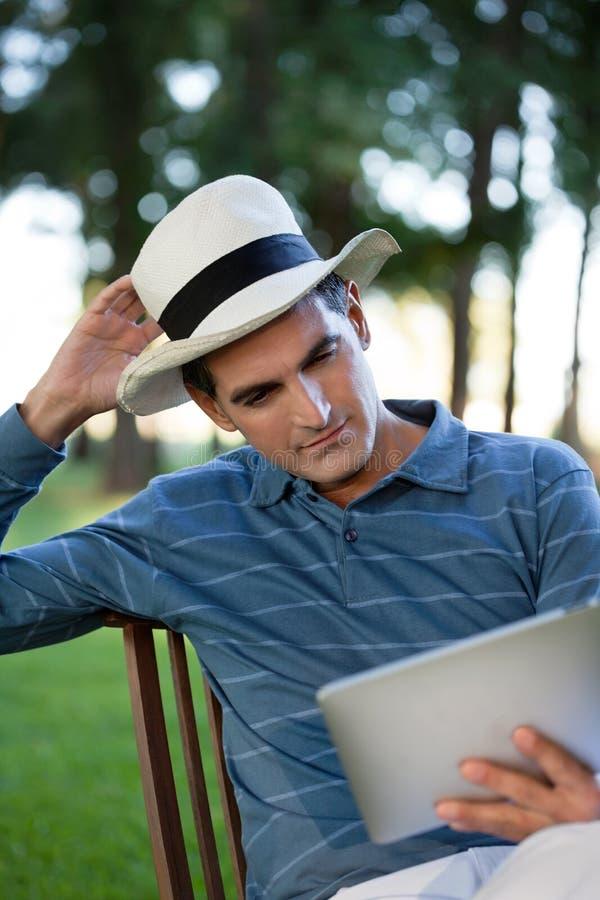 Homem que olha a tela do PC da tabuleta foto de stock royalty free