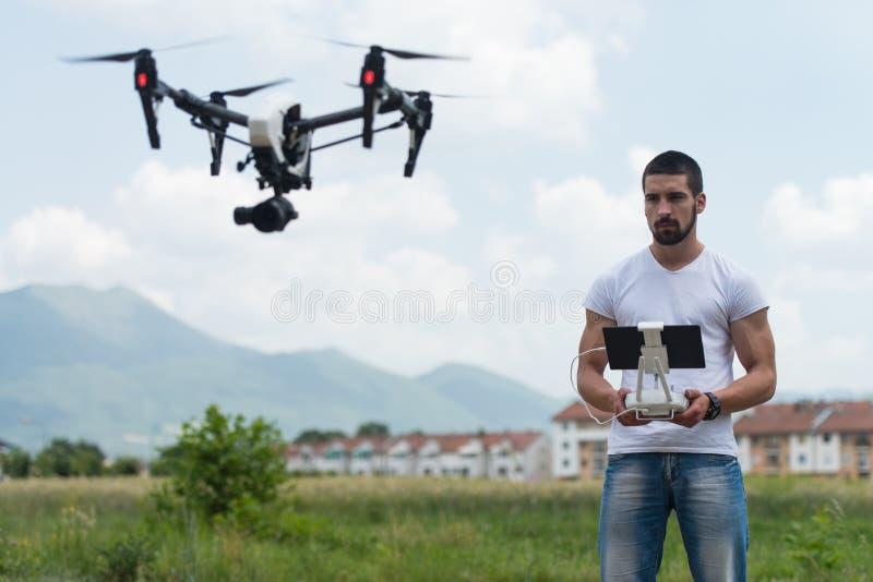 Homem que opera um zangão do voo no céu fotos de stock royalty free