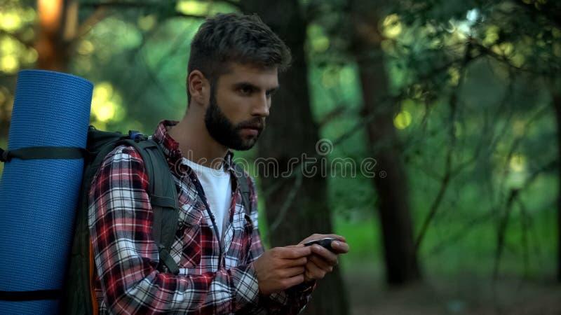 Homem que orienteering na floresta, usando o compasso navegacional, classes da sobrevivência imagem de stock