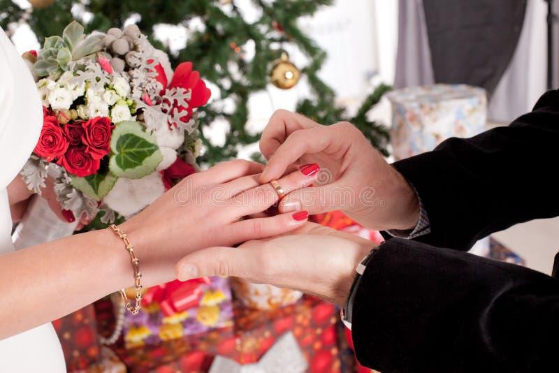 Homem que põe a aliança de casamento sobre a mão da mulher imagens de stock