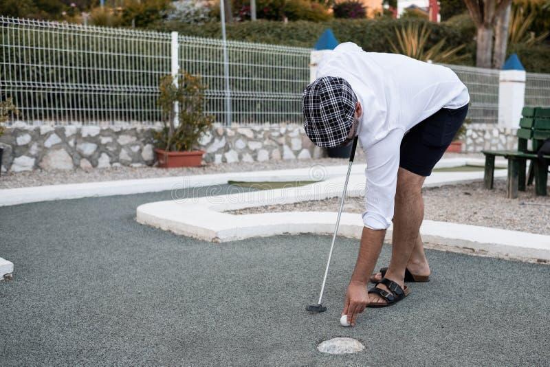 Homem que põe a bola de golfe ao lance fotografia de stock
