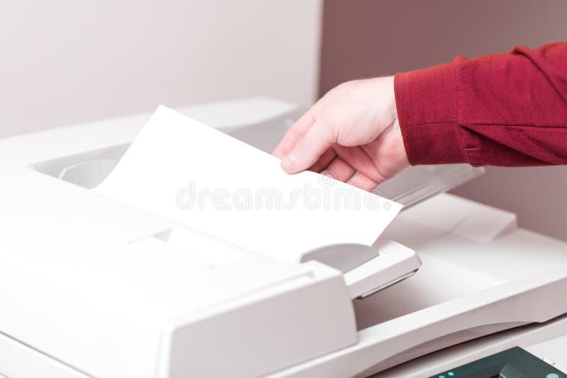 Homem que põe a folha de papel sobre a alimentação da impressora para fazer a varredura Conceito do trabalho de escritório fotos de stock royalty free