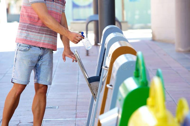 Homem que põe a garrafa plástica no escaninho de reciclagem foto de stock royalty free