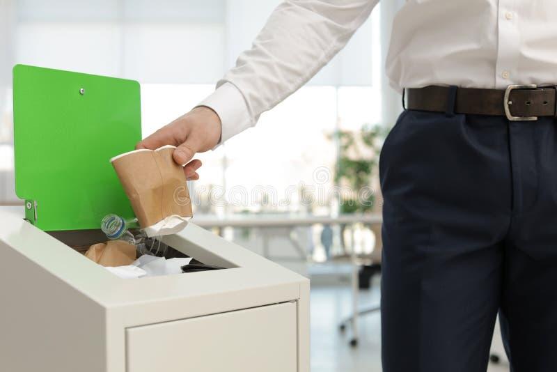 Homem que põe o copo de papel usado no escaninho de lixo no escritório Reciclagem de res?duos fotografia de stock royalty free