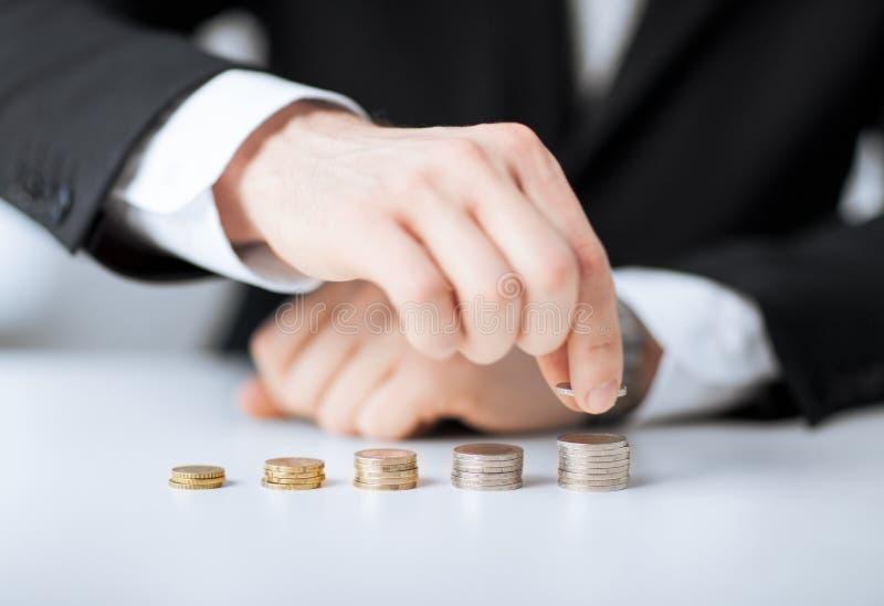 Homem que põe a pilha de moedas em uma fileira fotografia de stock royalty free