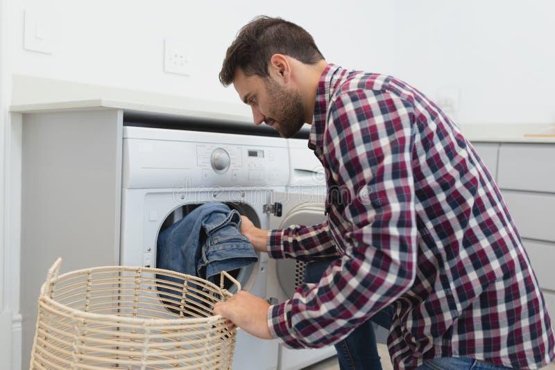 Homem que põe a roupa suja na máquina de lavar em uma casa confortável foto de stock