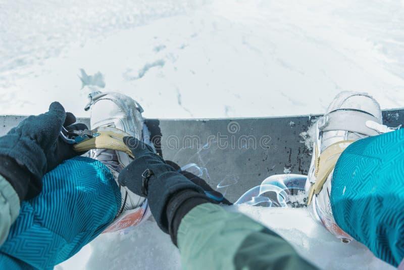 Homem que põe sobre seu snowboard foto de stock