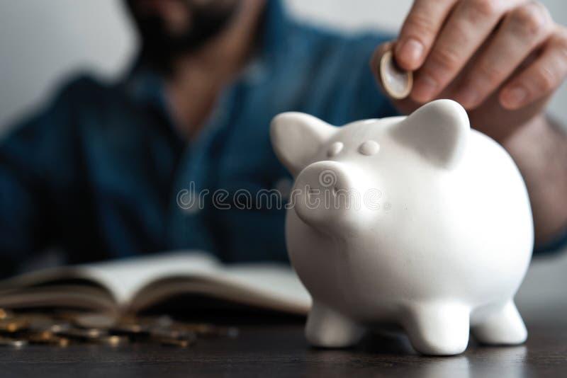 Homem que põr a moeda no banco piggy Conceito do dinheiro da economia fotos de stock royalty free
