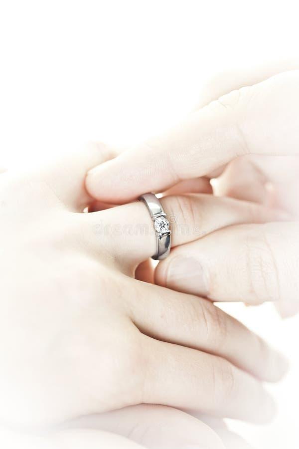 Homem que põr o anel de noivado sobre o dedo imagens de stock