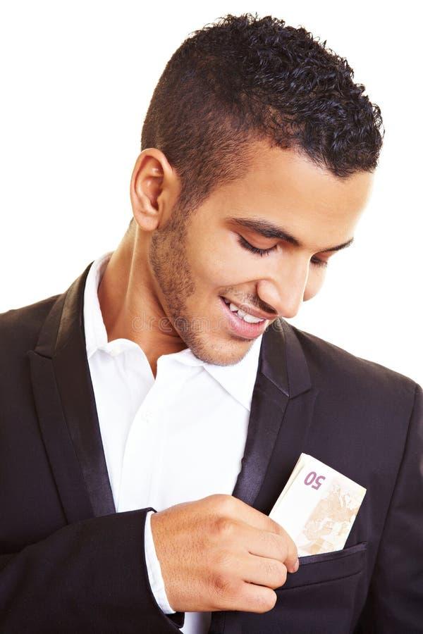 Homem que põr o dinheiro em seu bolso foto de stock royalty free