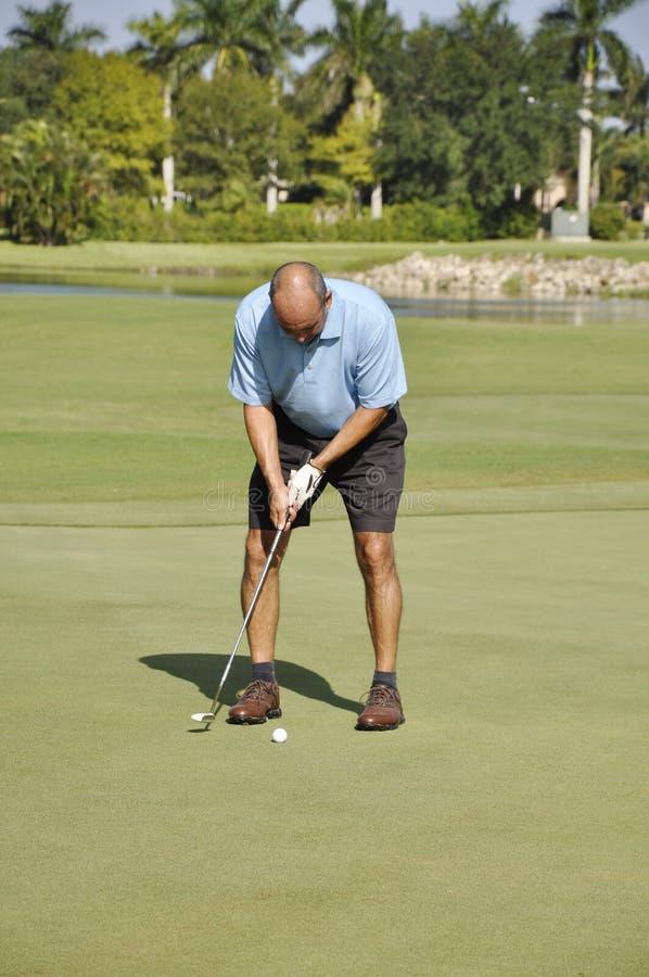 Homem que põr sobre um campo de golfe foto de stock royalty free