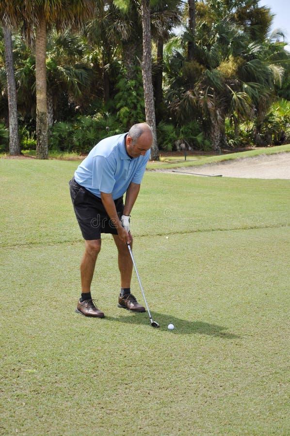 Homem que põr sobre um campo de golfe imagem de stock