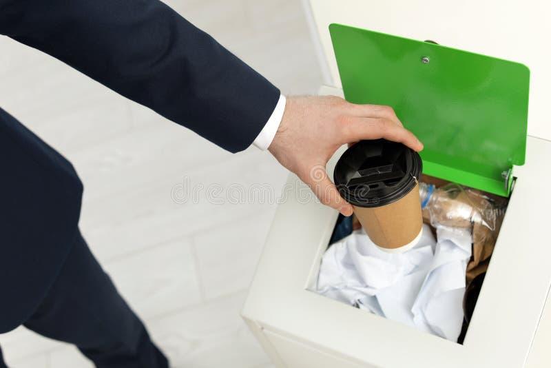 Homem que p?e o copo de papel usado no escaninho de lixo no escrit?rio Reciclagem de res?duos imagens de stock royalty free