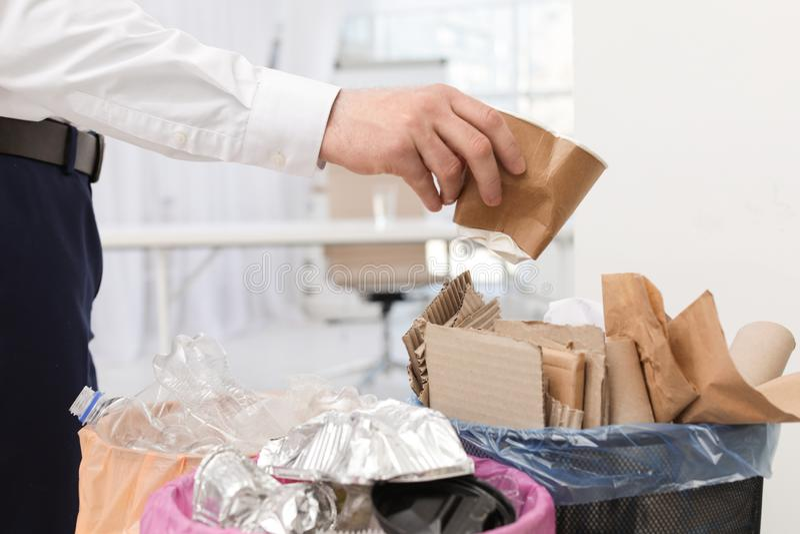 Homem que p?e o copo de papel usado no escaninho de lixo no escrit?rio Reciclagem de res?duos imagem de stock royalty free