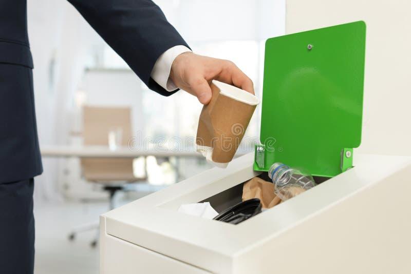 Homem que p?e o copo de papel usado no escaninho de lixo no escrit?rio Reciclagem de res?duos foto de stock royalty free