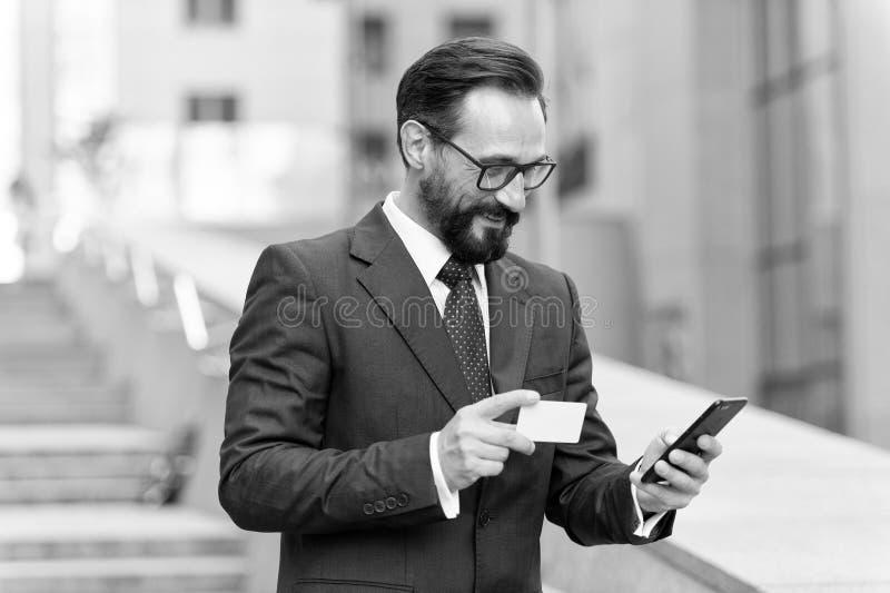 Homem que paga pelo cartão de crédito no telefone esperto fora do escritório Executivos maduros que fazem a ordem com o cartão de fotos de stock royalty free