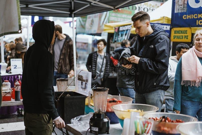 Homem que paga por seu alimento em um suporte da rua em New York fotos de stock royalty free