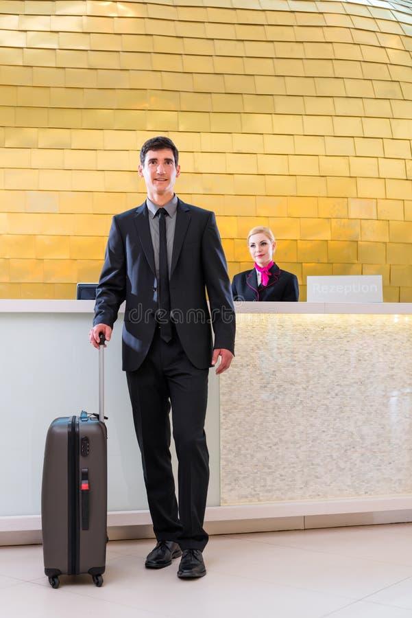 Homem que parte na viagem de negócios na recepção do hotel imagens de stock royalty free