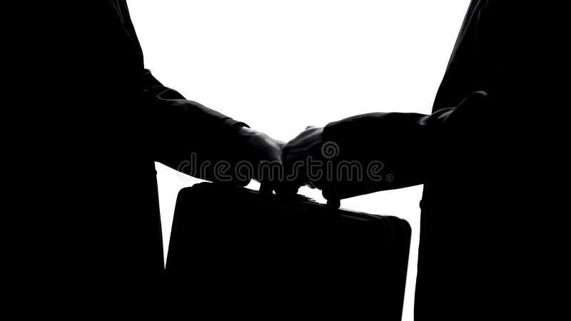 Homem que passa a mala de viagem ao sócio, ao acordo do negócio ou ao conceito financeiro da fraude imagens de stock