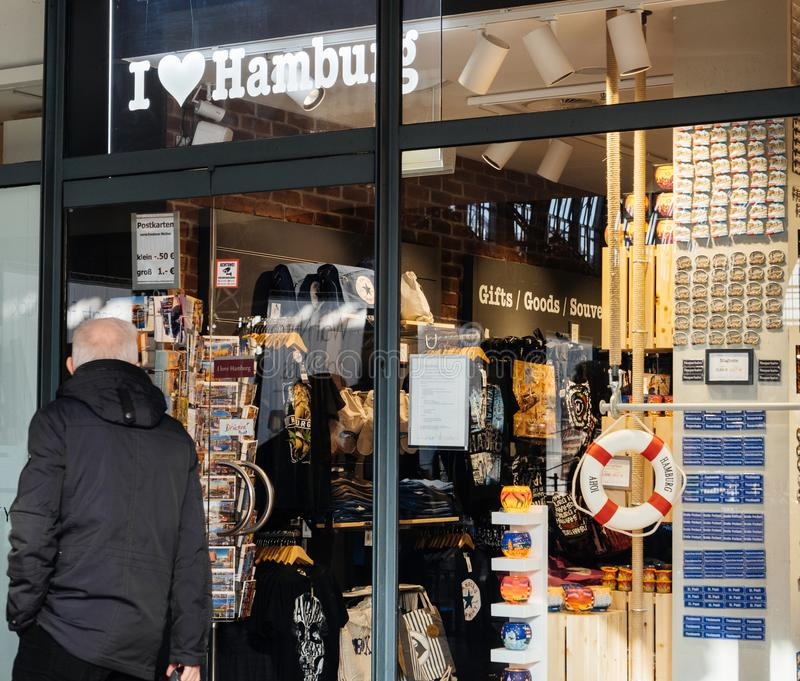 Homem que passa pela loja de lembrança no estação de caminhos de ferro de Hamburgo foto de stock