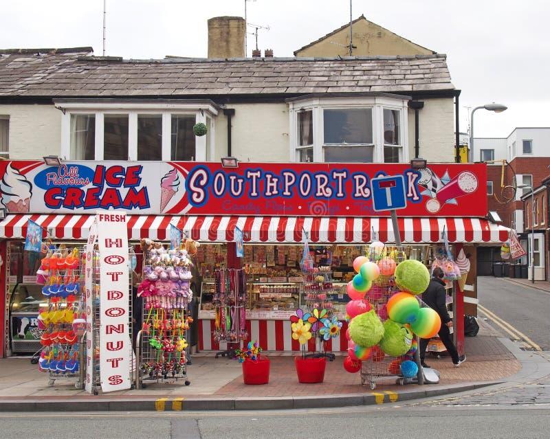 Homem que passa por uma loja na rua neville no sul do país vendendo donuts de sorvete e brinquedos de praia fotografia de stock royalty free