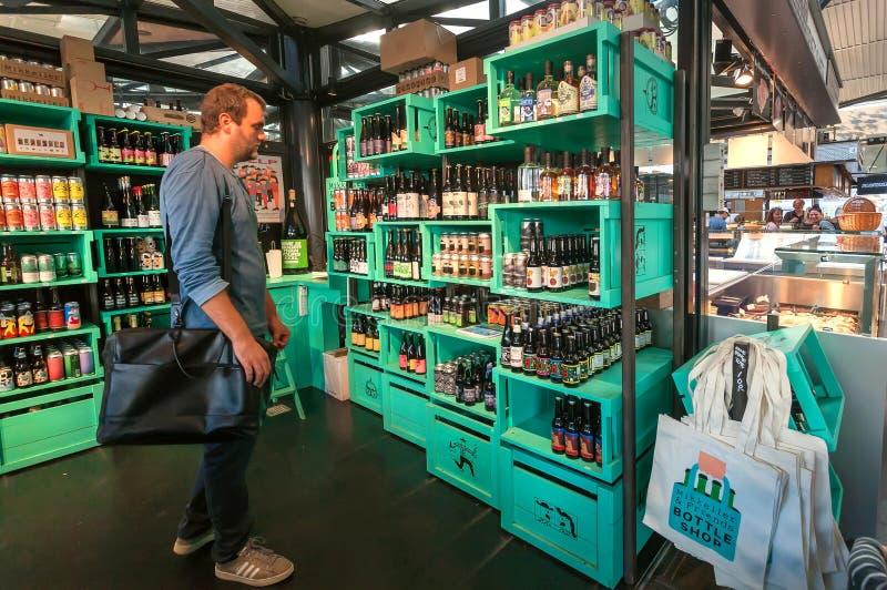 Homem que pensa sobre a cerveja dentro da loja colorida do projeto pela cervejaria popular de Mikkeller com escolha das garrafas fotos de stock