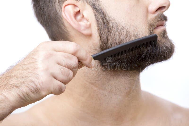 Homem que penteia sua barba imagem de stock