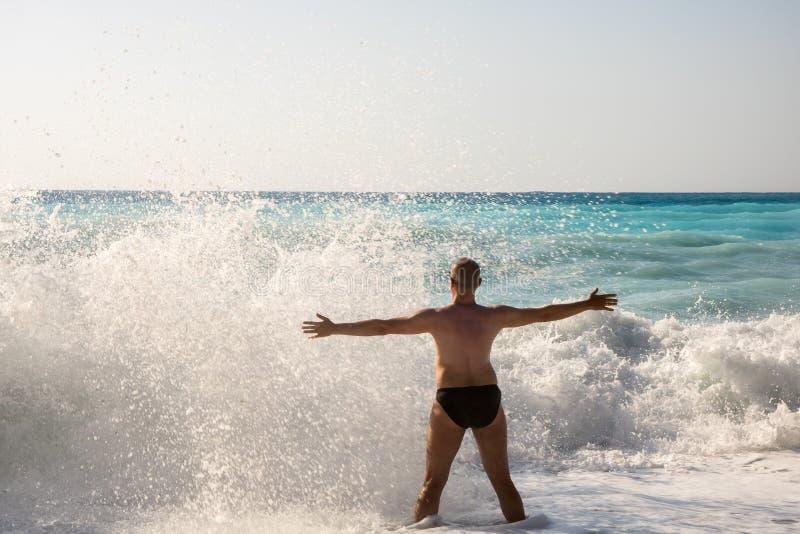 Homem que persegue as ondas na praia de Myrtos fotografia de stock royalty free