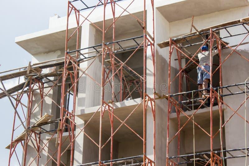 Homem que pinta o fundo da construção e do céu fotografia de stock royalty free