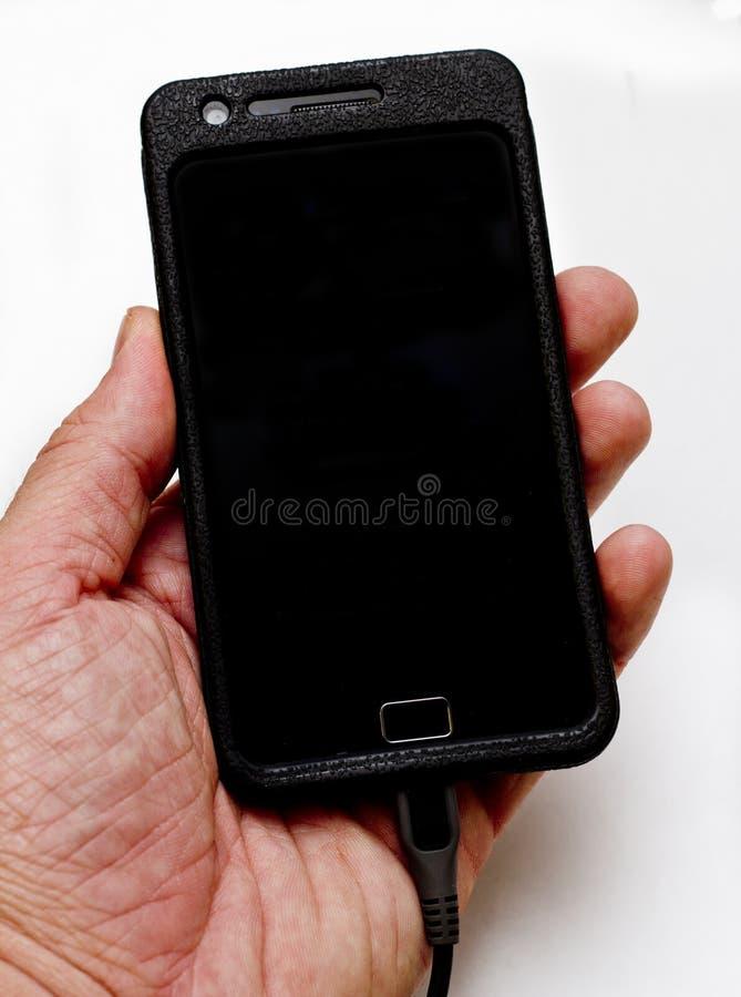 Homem que prende um telemóvel em sua mão imagens de stock