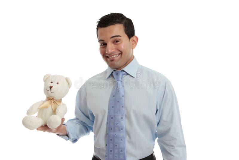 Homem que prende um urso de peluche feito malha foto de stock royalty free