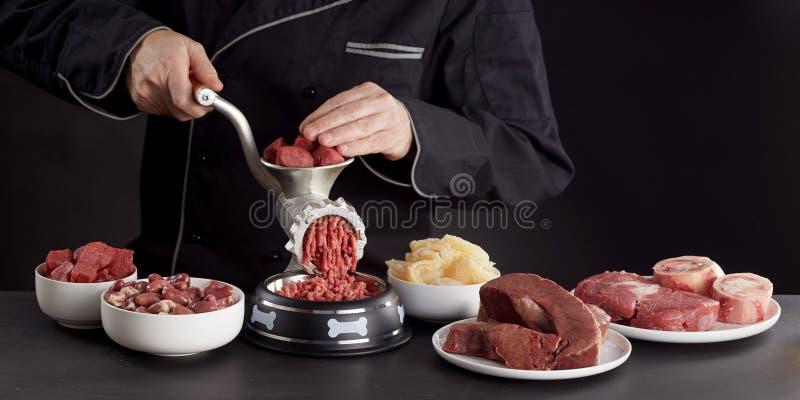 Homem que prepara a carne crua saudável para o alimento para cães do barf fotografia de stock royalty free