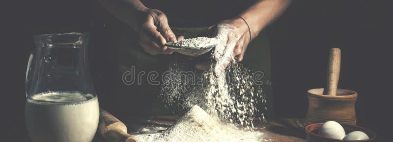 Homem que prepara a massa de pão na tabela de madeira em um fim da padaria acima Preparação do pão da Páscoa fotografia de stock royalty free