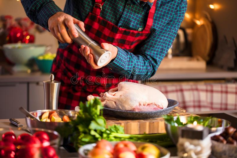 Homem que prepara o alimento delicioso e saudável na cozinha da casa para o pato ou o ganso do Natal do Natal imagem de stock