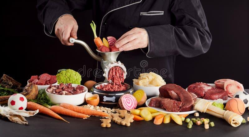 Homem que prepara o alimento saudável do barf para seu cão de estimação imagens de stock
