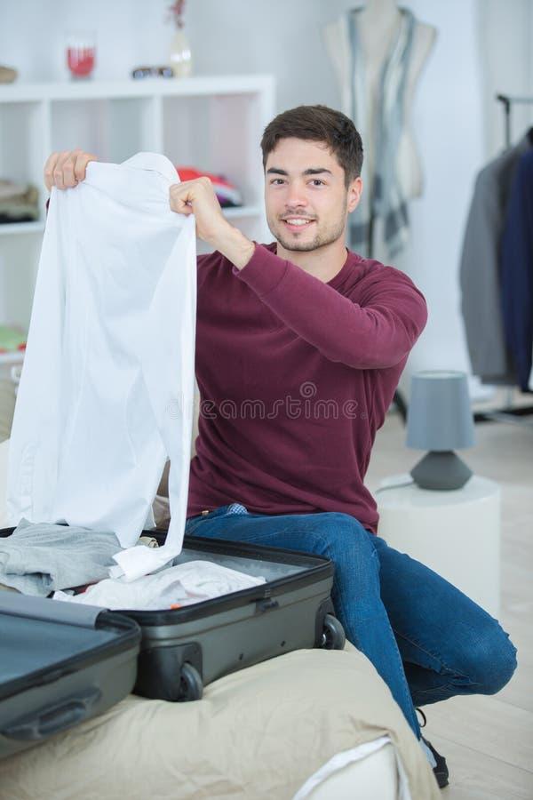 Homem que prepara sua bagagem imagens de stock royalty free