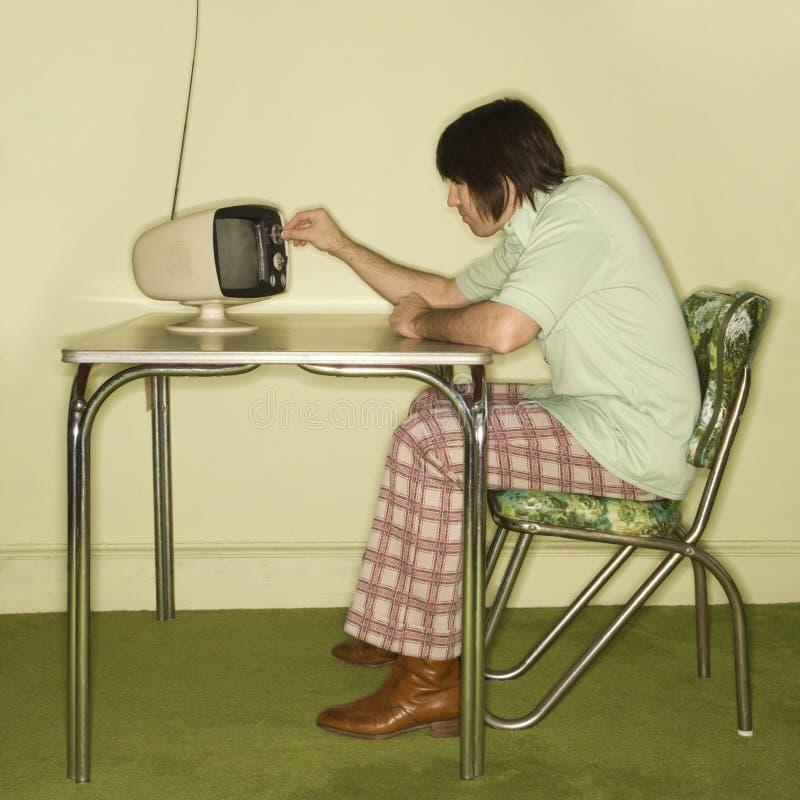 Homem que presta atenção à televisão velha. fotografia de stock
