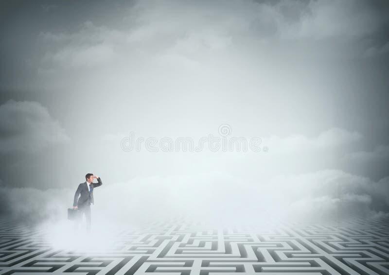 Homem que procura em um labirinto com nuvens fotografia de stock royalty free
