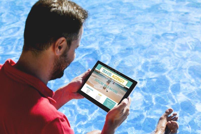 Homem que procura o destino do curso em um Web site da agência de viagens com uma tabuleta, ao sentar-se no lado da associação imagem de stock royalty free